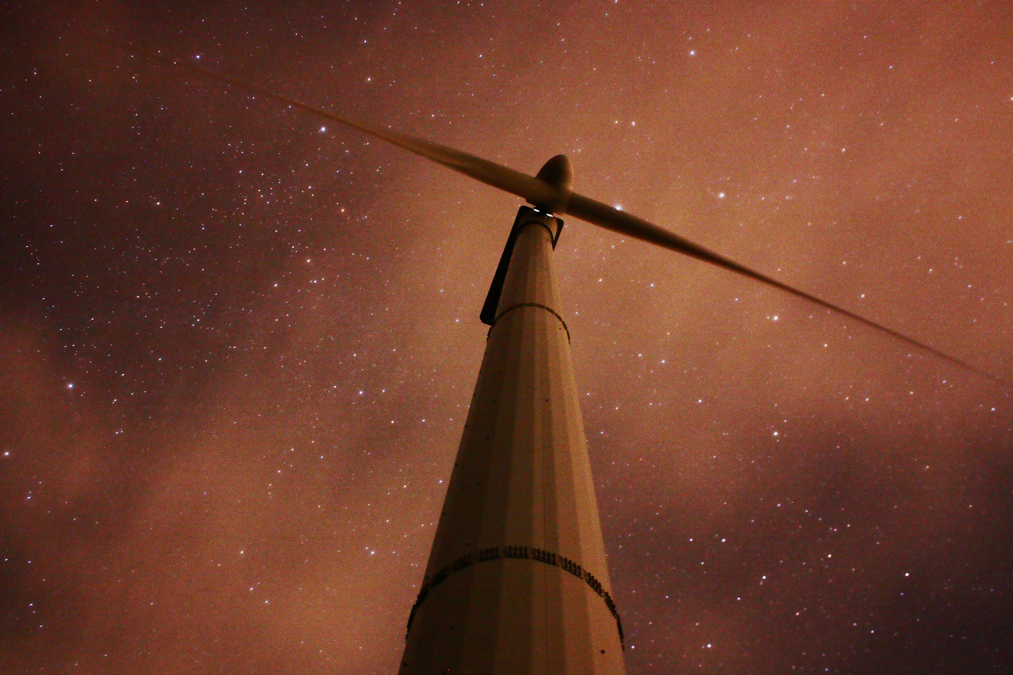 A wind turbine in front of a starry night sky, shot from a low angle.