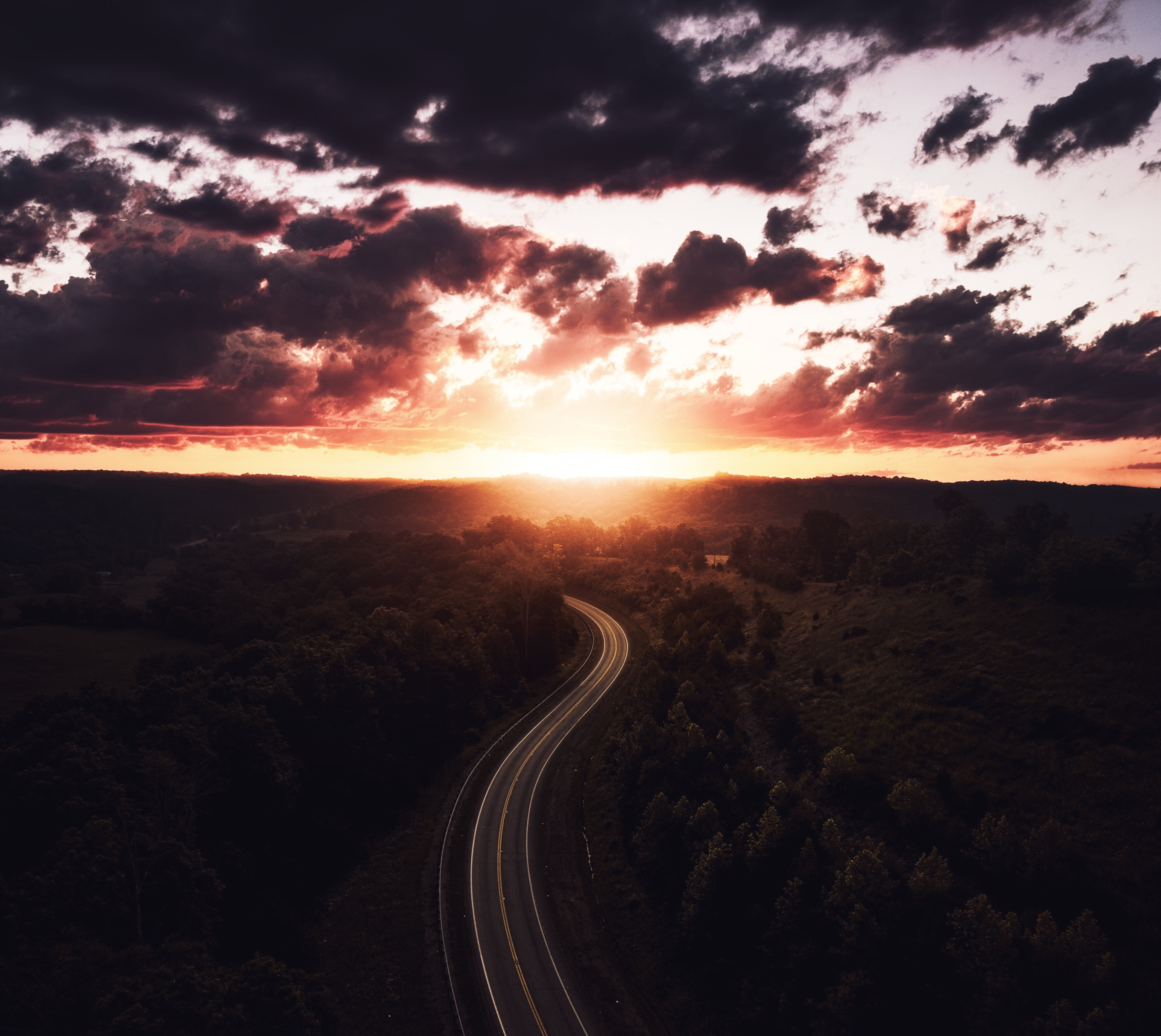 Sunset over a long, winding road.