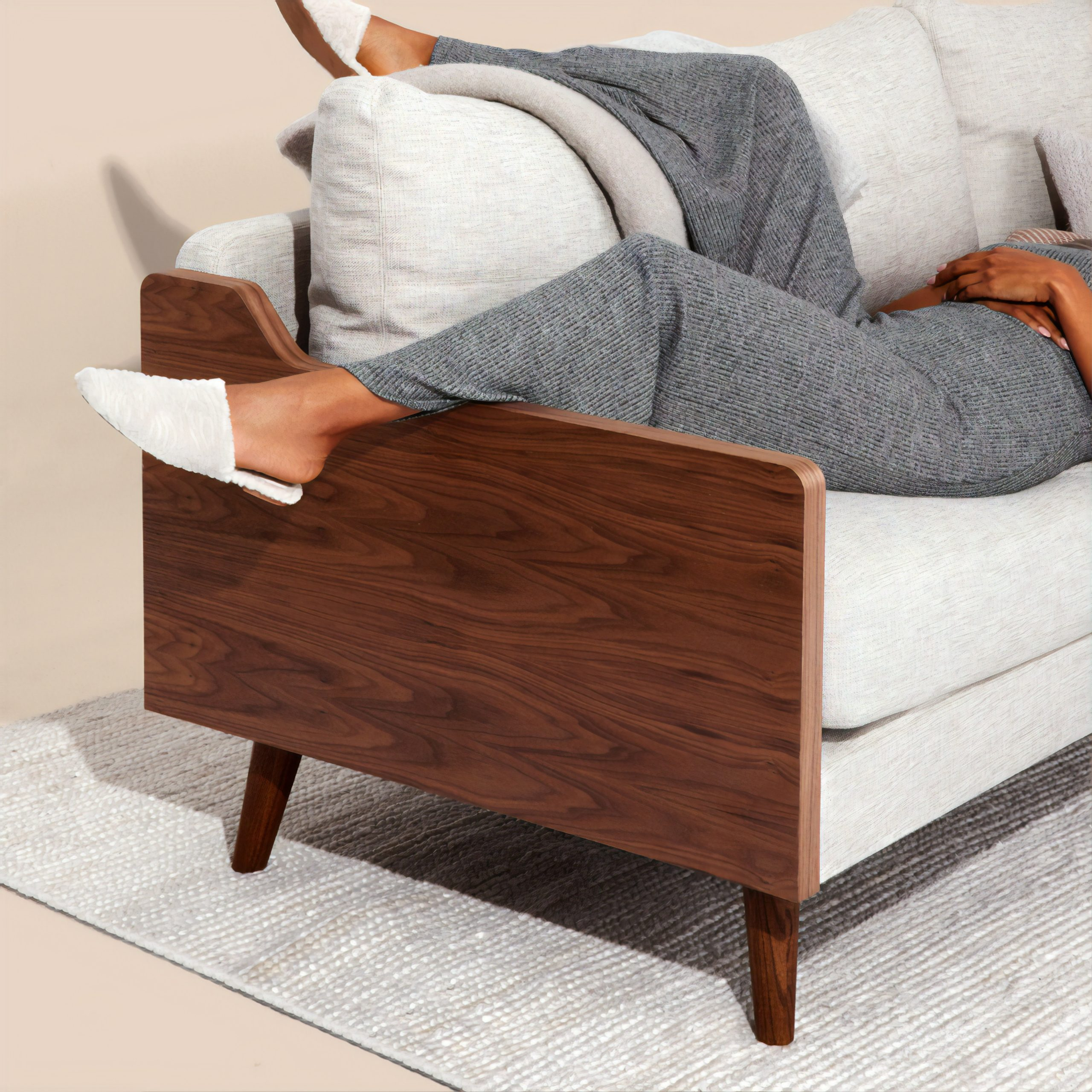 Women with brown skin lounging on a couch in comfortable clothes.