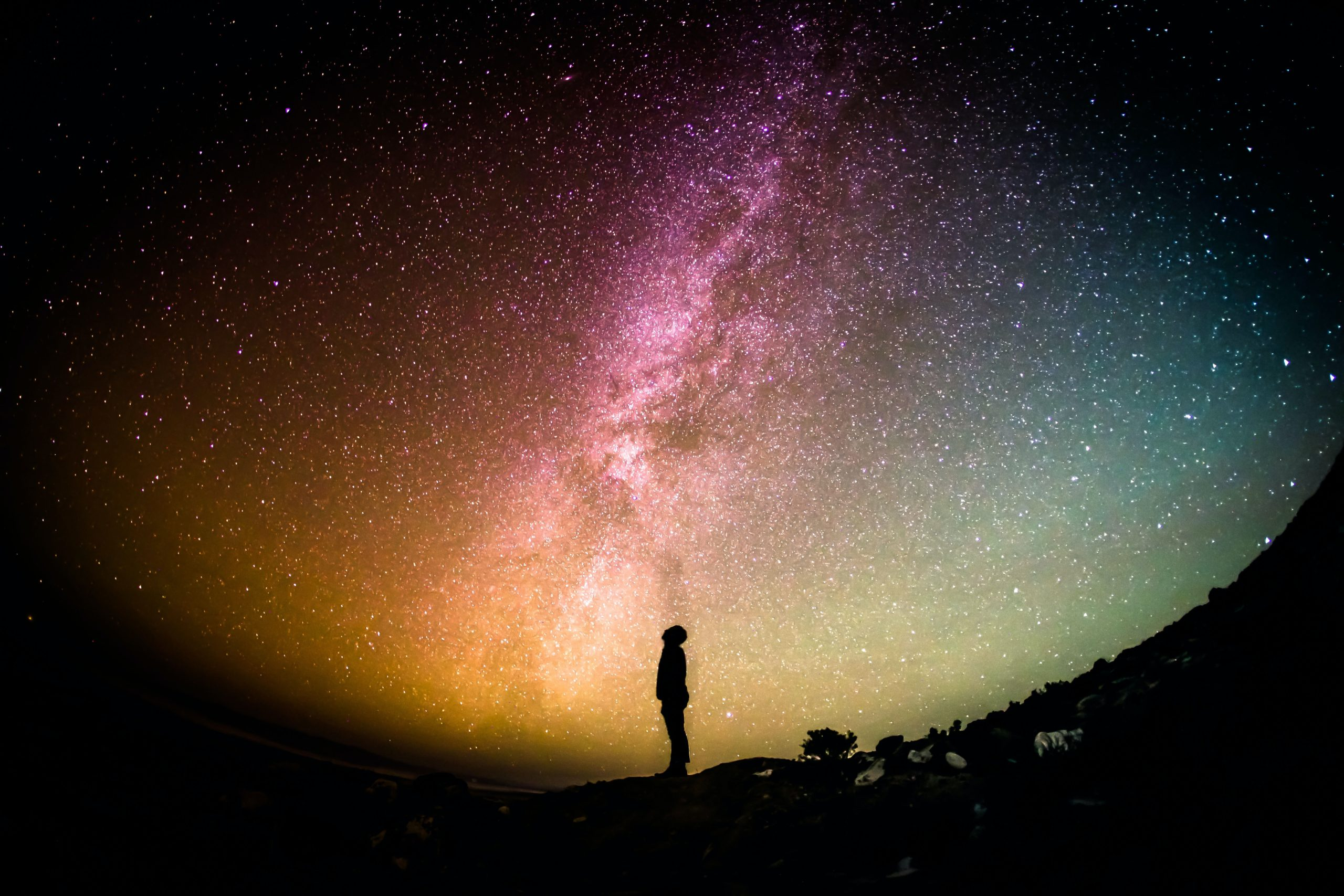 Person standing alone, staring up at a multi-colored galaxy of stars.