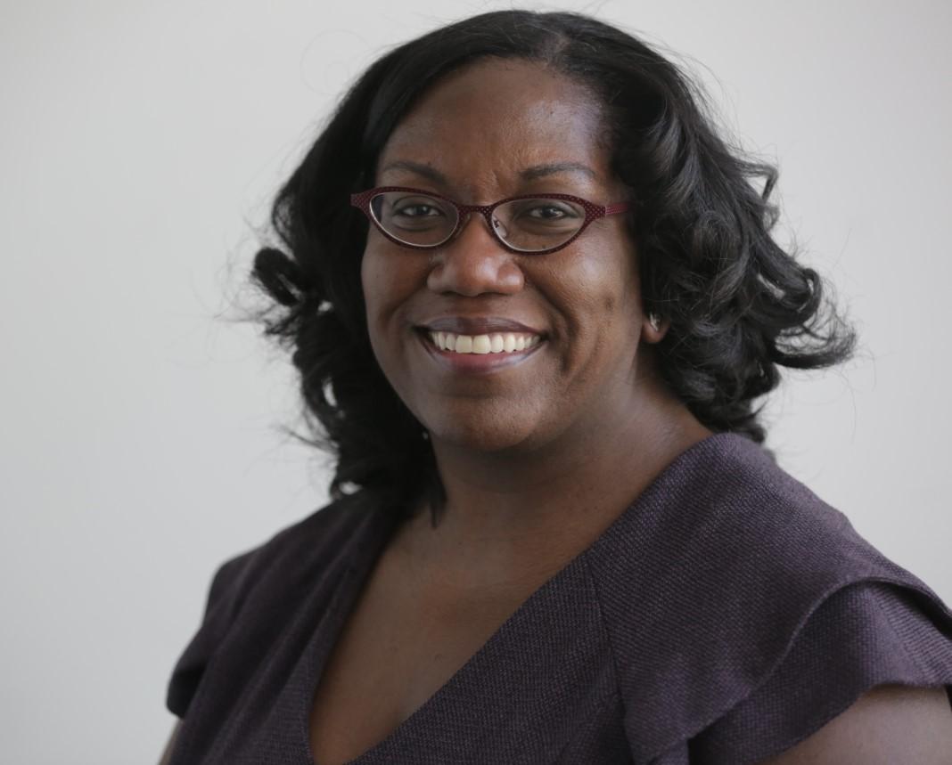 Kristin Mack, a smiling black woman in a dark purple top and glasses.
