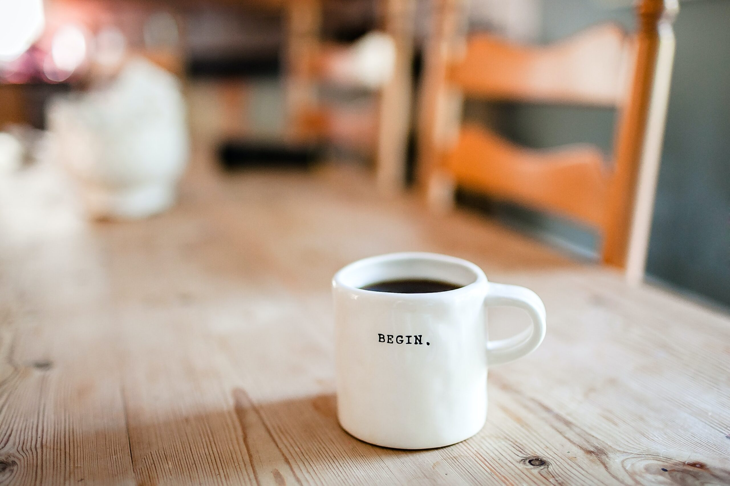 """White coffee mug that says """"Begin."""" on top of a wooden table."""