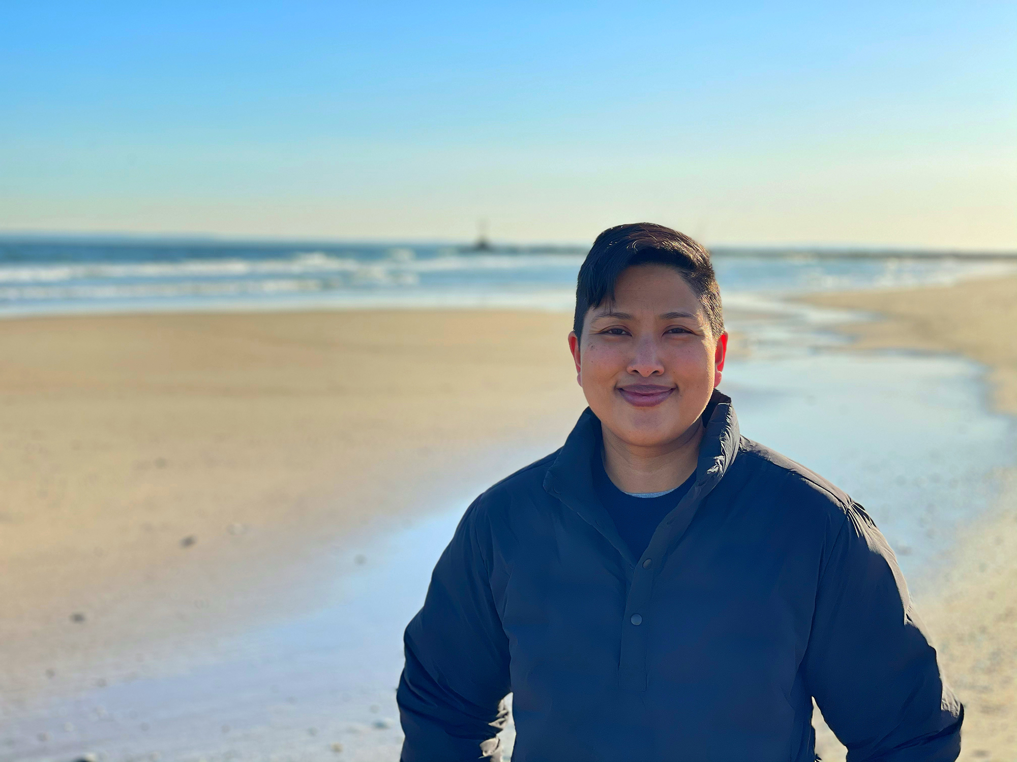 Bex Ahuja, a person of Asian descent, smiling on a beach.