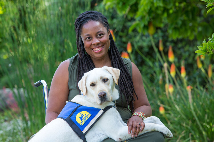 India Harville, African American female with long black locs, seated in her manual wheelchair wearing a long sleeveless green dress. Her service dog, Nico, a blond Labrador Retriever, has his front paws on her lap. He is wearing a blue and yellow service dog vest. They are outside with greenery behind them.